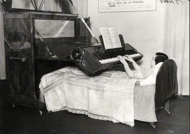 Lady lying in bed playing a piano